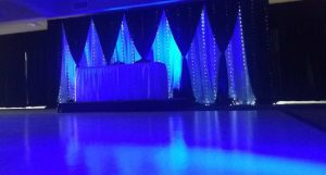Dance floor rental with black swagged curtains and colored lighting.